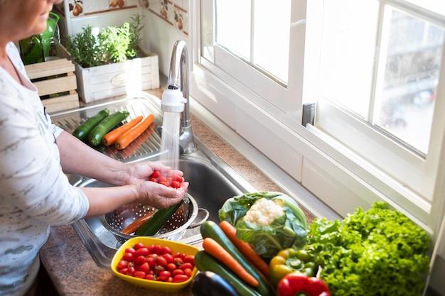 Een vrouw wast de oogst in de keuken kleine tomaten onder een waterstraal en veel groenten