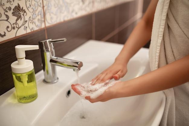 Een vrouw wast haar handen met zeep. middelen ter voorkoming van virussen en bescherming tegen ziektekiemen