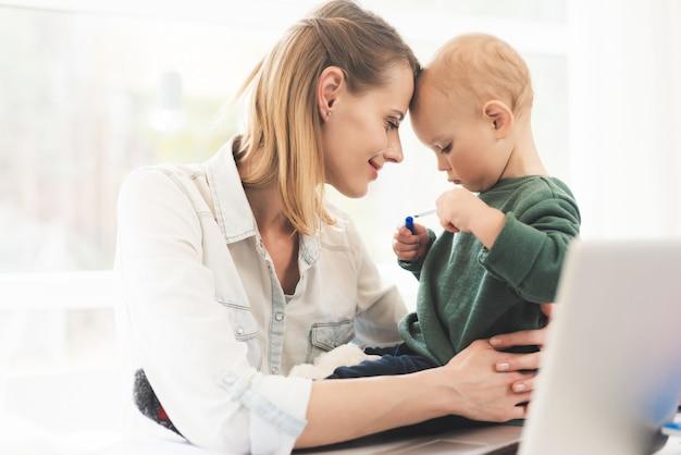 Een vrouw werkt en zorgt tegelijkertijd voor een kind.