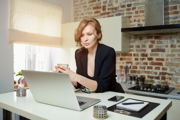Een vrouw werkt op afstand op een laptop in een keuken. een meisje houdt een glas koffie terwijl ze luistert naar het verslag van haar collega tijdens een videoconferentie thuis.