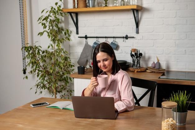 Een vrouw werkt op afstand van huis in de keuken op kantoor, zittend achter de computer. afstandsonderwijs, online onderwijs en werk. meisje student bereidt zich voor op examens.
