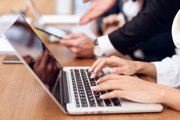 Een vrouw werkt op een laptop. het drukt op het toetsenbord.