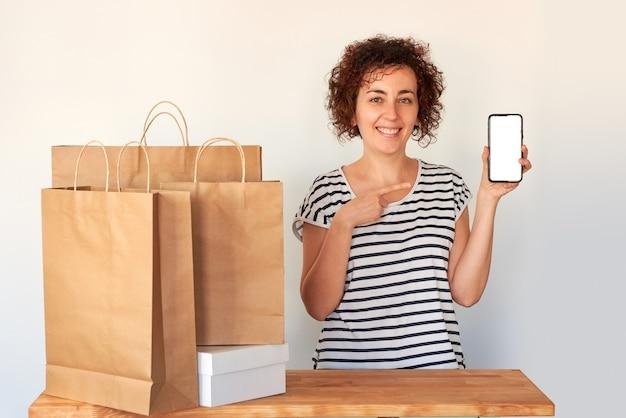 Een vrouw wijst naar haar mobiele telefoon naast een paar boodschappentassen