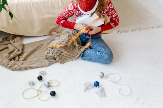 Een vrouw wikkelt een lint rond kerstcadeau zittend op de vloer
