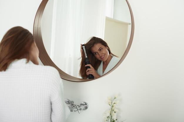 Een vrouw windt haar haren op met een föhn in de badkamer. mooie dame doet haar haar thuis