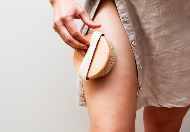 Een vrouw zal een droge lichaamsmassage doen met een natuurlijke borstel. schoonheid en verzorging. kopieer ruimte