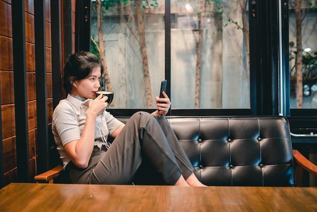 Een vrouw zat in een coffeeshop met een koptelefoon aan de telefoon en een medisch masker om covid-19 te beschermen.