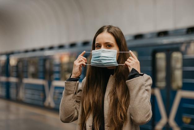 Een vrouw zet een medisch masker op haar gezicht om verspreiding van het coronavirus in een metrostation te voorkomen. een meisje met lang haar in een jas wacht op een trein op een metroplatform.