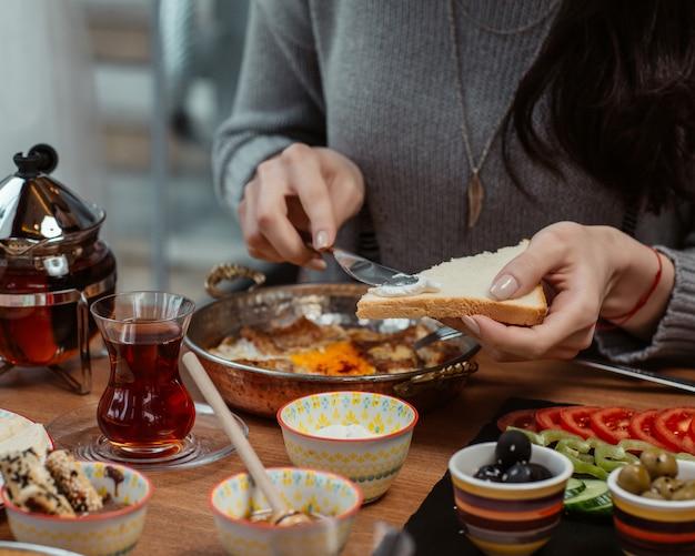Een vrouw zet room en honing op een sneetje brood rond een ontbijttafel met veel voedsel.