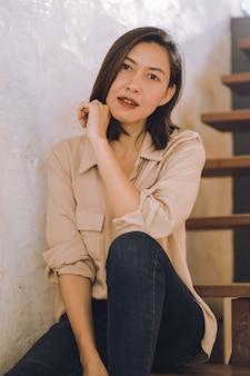 Een vrouw zit aan een oude houten trap