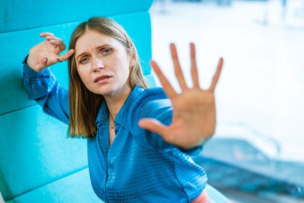 Een vrouw zit bij het raam en toont een handgebaar van nee en verzet kaukasisch meisje in een blauwe d...