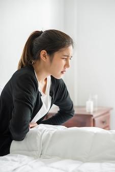 Een vrouw zit in bed met buikpijn en drukt haar hand op haar buik.