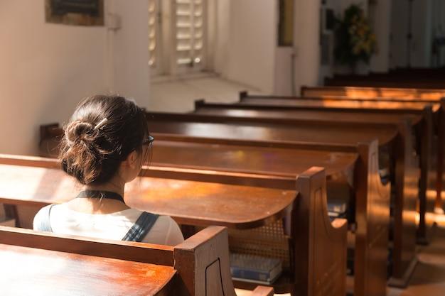 Een vrouw zit in de kerk.