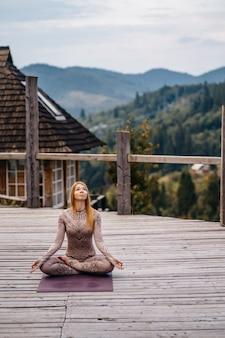 Een vrouw zit in de lotuspositie in de ochtend op een frisse lucht.