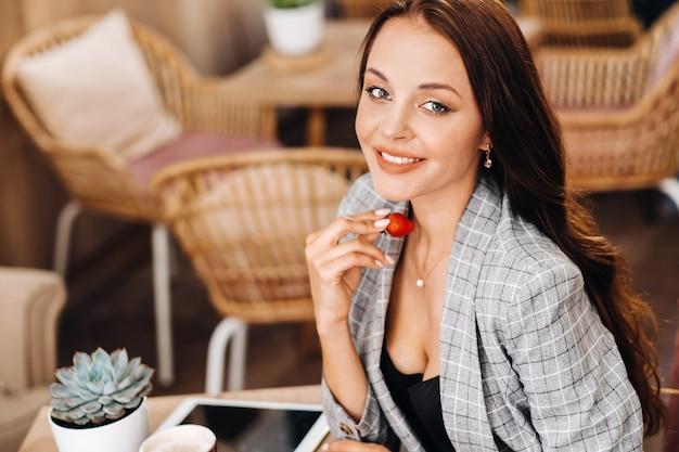 Een vrouw zit in een café en eet aardbeien. een meisje met aardbeien in haar handen in een coffeeshop.