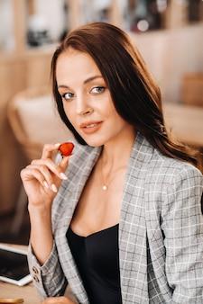 Een vrouw zit in een café en eet aardbeien. een meisje met aardbeien in haar handen in een koffieshop.