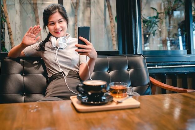 Een vrouw zit in een café met koptelefoon videobellen medische bescherming om covid-19 te beschermen