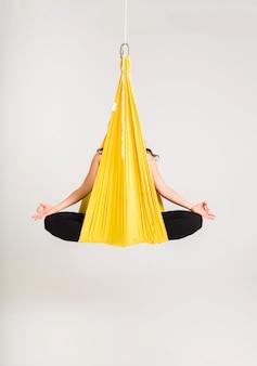 Een vrouw zit in een gele hangmat in de padmasana pose op een witte muur