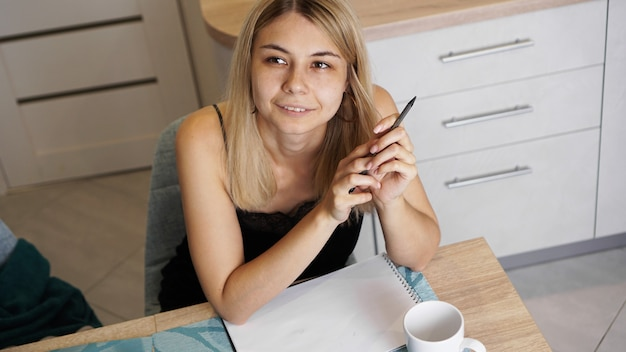 Een vrouw zit in een lichte keuken en schrijft een brief of haar wensen. een meisje droomt. op tafel staat een kopje koffie.
