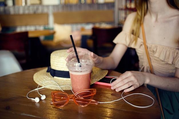 Een vrouw zit in een restaurant met koptelefoon een glas verse glazen vrijetijdsbesteding. hoge kwaliteit foto