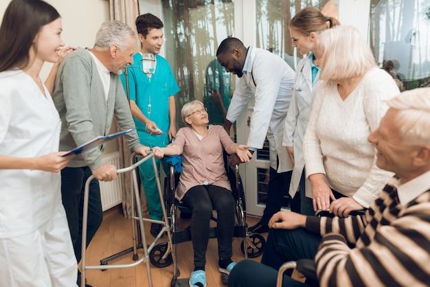 Een vrouw zit in een rolstoel met medische druppelaar.