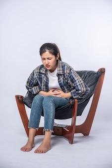 Een vrouw zit in een stoel met buikpijn en drukt haar hand op haar buik