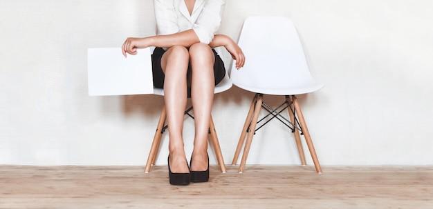 Een vrouw zit in een stoel met een cv in handen in afwachting van een interview.