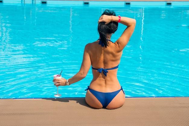 Een vrouw zit in het zwembad met haar rug naar een koud drankje. zomer blauw water