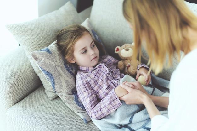 Een vrouw zit naast een klein meisje dat ziek is