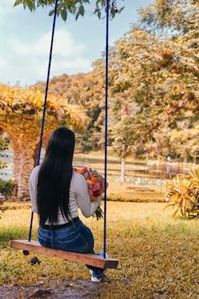 Een vrouw zit oa schommel met een boeket bloemen