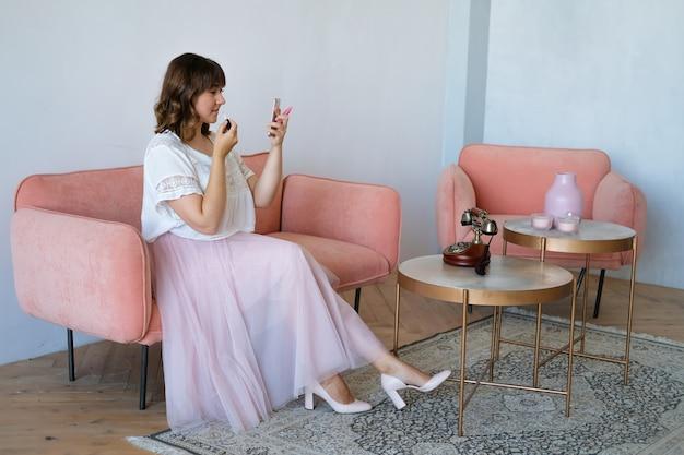 Een vrouw zit op de bank in de kamer en schildert haar lippen