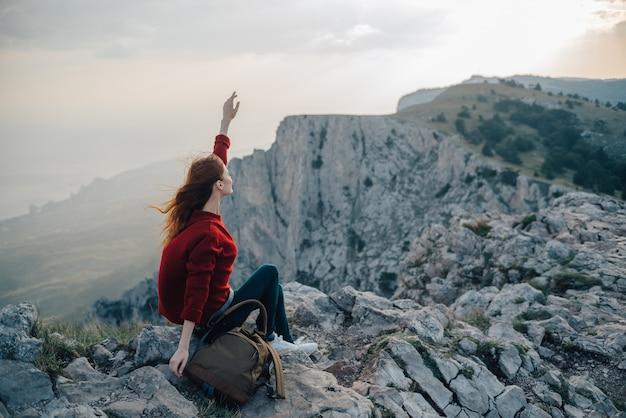 Een vrouw zit op de rand van een klif, een toeristenreiziger kijkt naar de zonsondergang