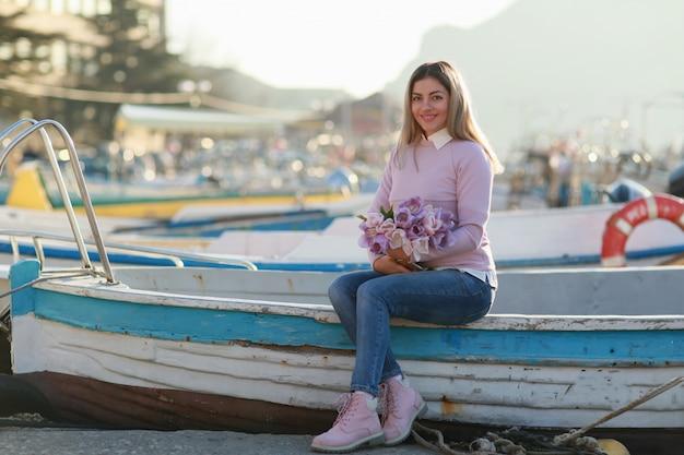 Een vrouw zit op een vissersboot in de baai met vissersboten