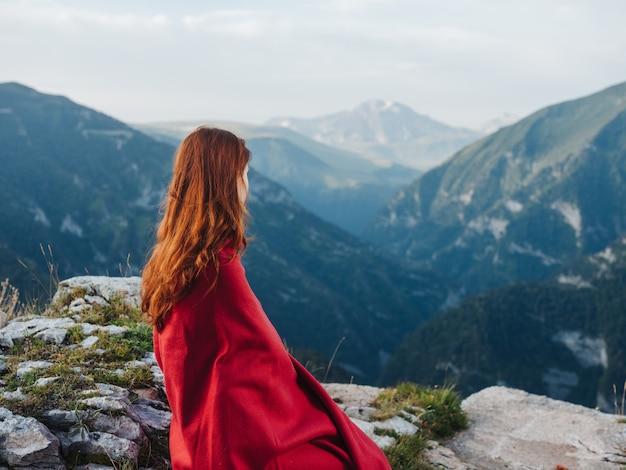 Een vrouw zit op stenen bedekt met een rode deken buiten in de bergen. hoge kwaliteit foto