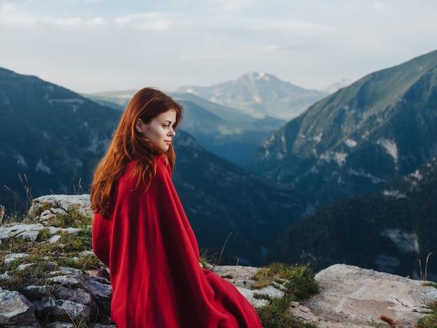 Een vrouw zit op stenen bedekt met een rode deken buiten in de bergen