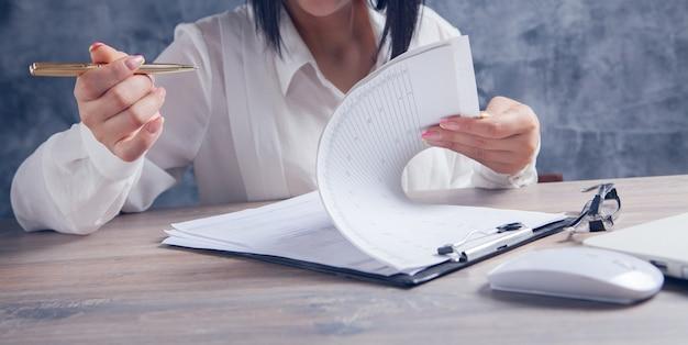 Een vrouw zit voor een laptop en bestudeert documenten