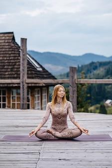 Een vrouw zittend in lotushouding in de ochtend op een frisse lucht.
