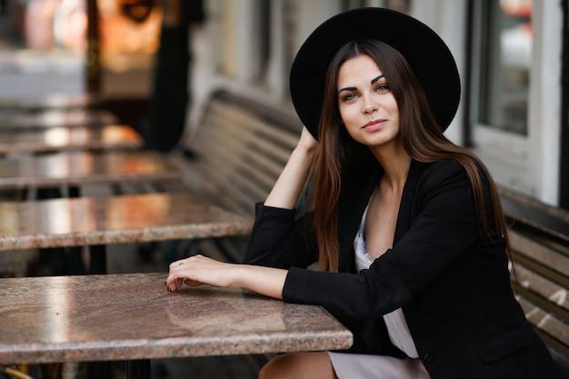 Een vrouw zittend op een bankje in de buurt van het café. hoge kwaliteit