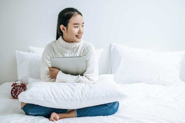 Een vrouw zittend op het bed, de laptop knuffelen en glimlachen.
