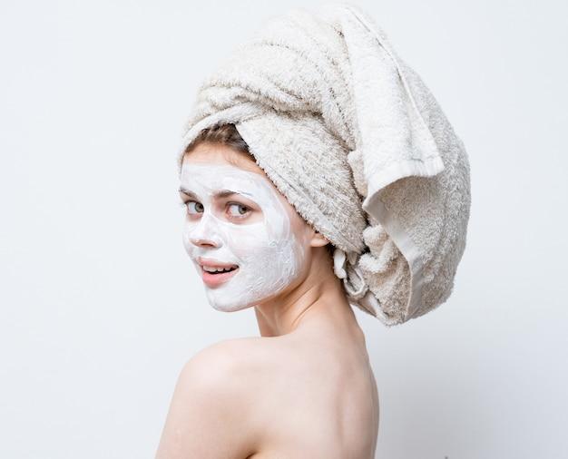 Een vrouw zorgt voor haar uiterlijk en een handdoek op haar hoofd en een vochtinbrengende crème op haar gezicht.