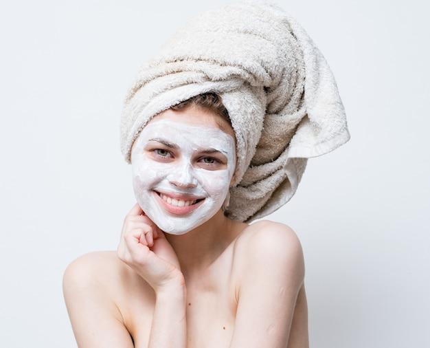 Een vrouw zorgt voor haar uiterlijk en een handdoek op haar hoofd en een vochtinbrengende crème op haar gezicht