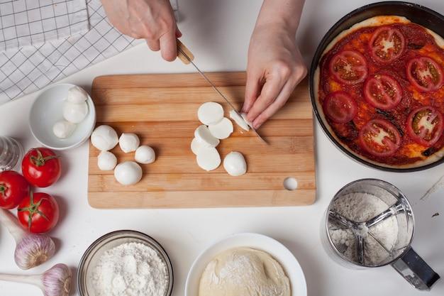 Een vrouwchef-kok snijdt mozarellakaas.