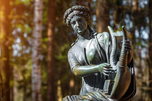 Een vrouwelijk koperen beeld van een god met een harp in het bos