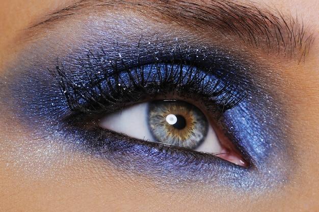 Een vrouwelijk oog met helderblauwe oogschaduw - macrospruit