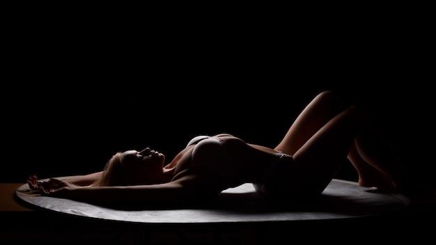 Een vrouwelijk silhouet op een zwarte achtergrond ligt, slanke vrouw. verleidelijke pose