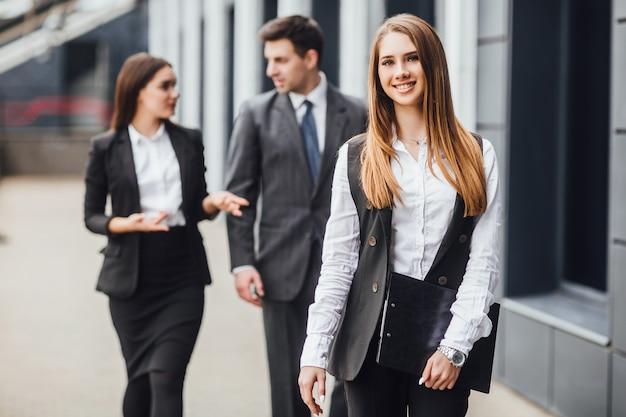 Een vrouwelijke advocaat staat voor een gerechtsgebouw of gemeentelijk gebouw met haar armen over elkaar.