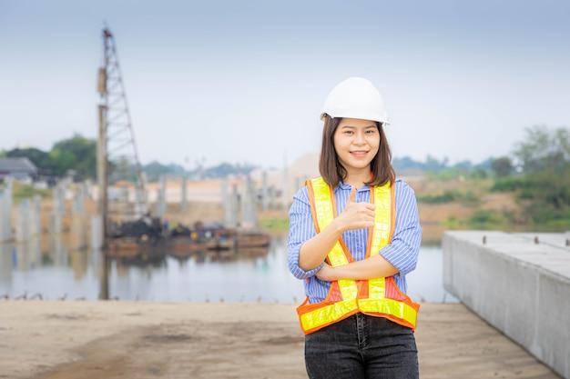 Een vrouwelijke architectenleider die bij de brugconstructie staat, een veiligheidshelm draagt en de blauwdruk van het project vasthoudt