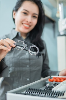 Een vrouwelijke arts die een oogtest meethulpmiddel in een oogkliniek met de achtergrond van de arts houdt