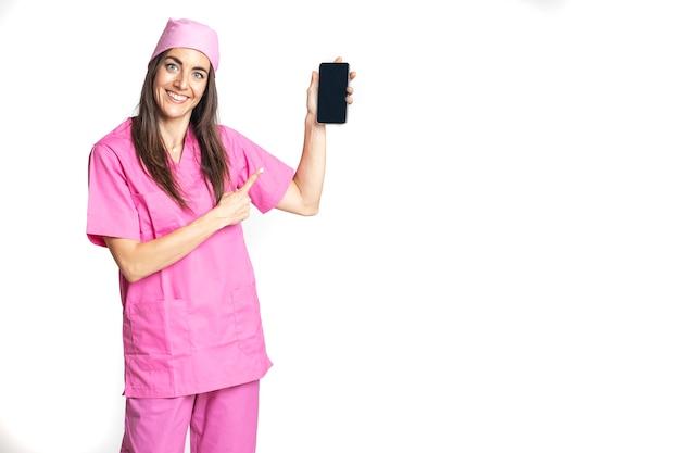 Een vrouwelijke arts die in een ziekenhuis of kliniek werkt, glimlacht vriendelijk en geeft aan dat ze haar mobiele telefoon vasthoudt