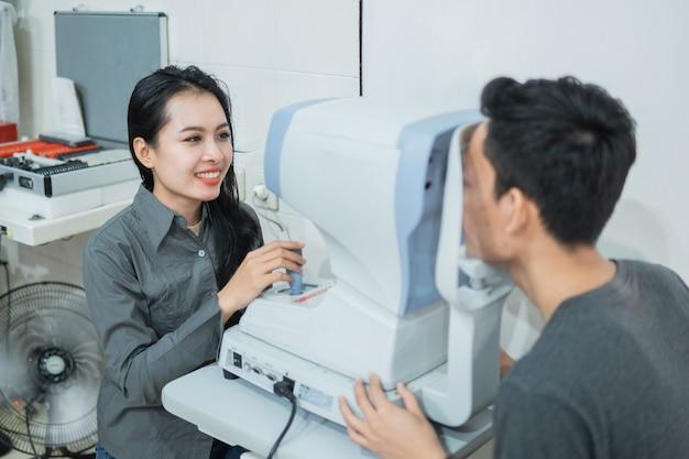 Een vrouwelijke arts en een mannelijke patiënt doen een oogcontrole met behulp van een apparaat in een oogkliniek